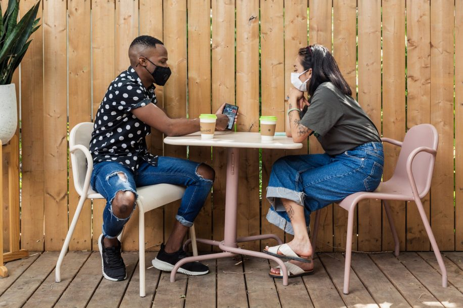 students-drinking-coffee-on-a-patio-with-face-masks